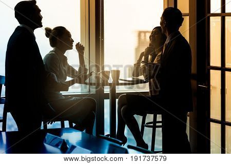 Group of office employees having coffee break and talking about business, filtered image
