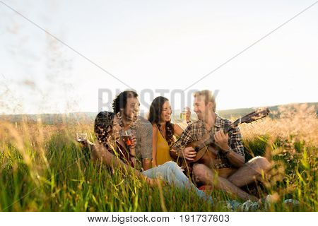 Friends sitting together in grass playing guitar and chilling