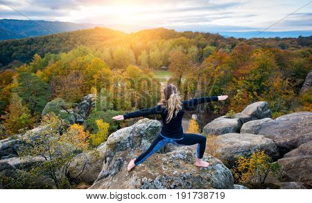 Sporty Fit Woman Is Practicing Yoga And Doing Asana Virabhadrasana 2 On The Top Of The High Rocky Mo