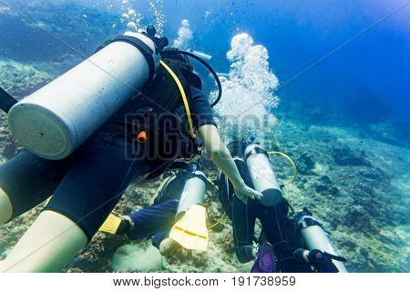 Two divers scuba diving in tropical sea at reef underwater