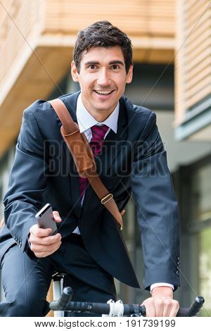 Confident multitasking young businessman using a mobile phone while riding a bicycle to work