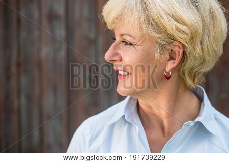 Side view close-up portrait of a serene nostalgic senior woman looking away with a smile while daydreaming outdoors