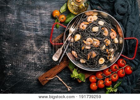 Black spaghetti with prawns and scallop in frying pan on black background, top view with copy space