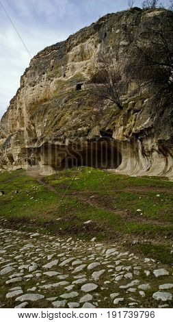 The cave is on a hillside in the ancient town Chufut-Kale in Crimea, near Bakhchisarai. Vertical view