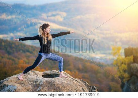 Attractive Slim Girl Is Practicing Yoga And Doing Asana Virabhadrasana 2 On The Top Of The Mountain