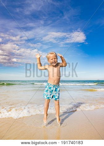 Cute boy jumping on the beach