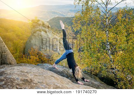 Sporty Fit Woman Is Practicing Yoga And Doing Asana Adho Mukha Shvanasana On The Top Of The Mountain