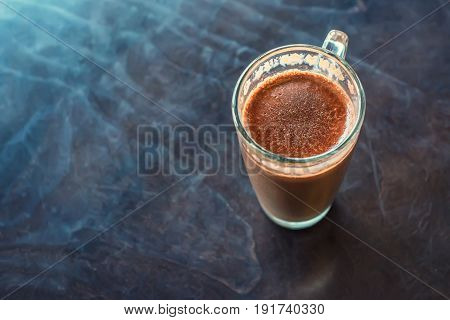 Top view of glass with chocolate milk drink on table
