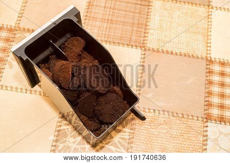 Closeup image of metal container part of coffee machine with coffee grounds in it