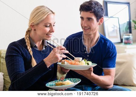 Young Caucasian couple eating Asian traditional food with chopsticks while sitting on the couch at home