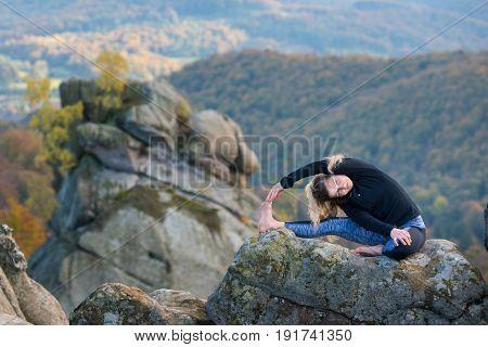 Flexible Fit Girl Is Practicing Yoga Asana Pavravrtta Janu Shirshasana On The Top Of The Mountain. A