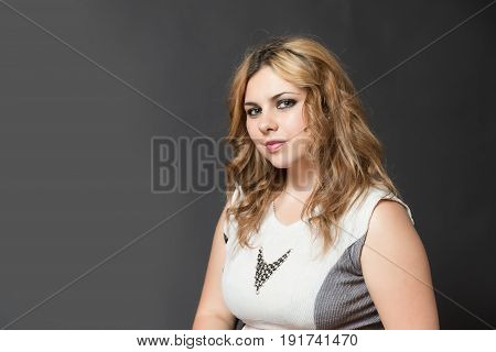 Portrait of attractive long haired young woman looking sideways at the camera. All is on the gray background.