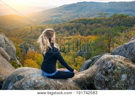 Peaceful Fit Female Is Practicing Yoga And Doing Asana Siddhasana On The Top Of The High Rocky Mount