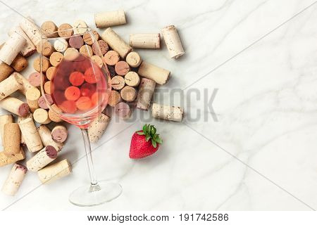 A high-key overhead photo of a glass of rose wine with corks and a fresh strawberry, on a white marble texture with a place for text