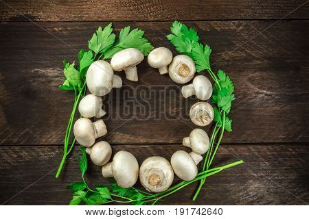 An overhead photo of fresh white mushrooms with green parsley, forming a circle frame on a dark rustic texture with a place for text