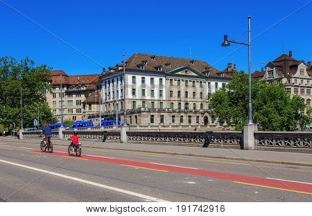 Zurich, Switzerland - 18 June, 2017: bicyclists on Rudolf Brun bridge, buildings along the Limmat river. Zurich is the largest city in Switzerland and the capital of the Swiss canton of Zurich.