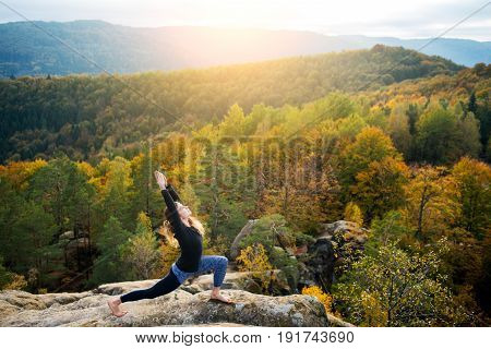 Happy Fit Woman Is Practicing Yoga And Doing Asana Virabhadrasana 1 On The Top Of The High Rocky Mou