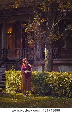 Beautiful young woman in long skirt and wool scarf standing near old house. Early fall. Outside shot. Ambient light.