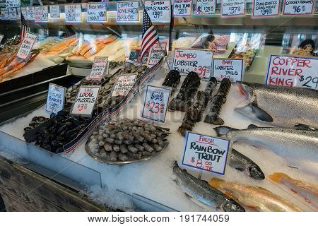 Fresh seafood stall with Salmon Lobster Prawns Clams Crabs Octopus Oyster at public market in Seattle Washington