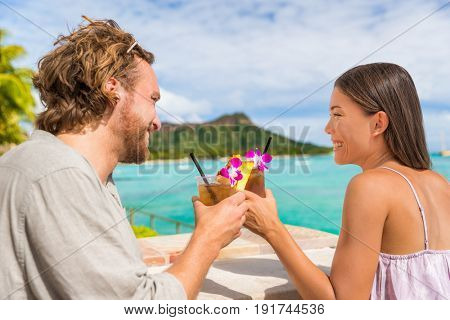 Couple toasting drinks flirting on date at beach bar in Waikiki, Honolulu,Hawaii. Young people going out drinking mai tai drink alcoholic cocktails.