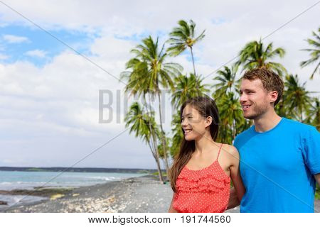 Interracial couple on Hawaii holiday enjoying view of ocean from black sand volcanic beach on Big Island of Hawaii, hawaiian vacation destination.
