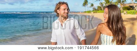 Banner couple lifestyle enjoying sunset walk on beach holidays. Horizontal panorama crop of young people in love relaxing, summer vacation travel. Asian woman, caucasian man interracial relationship.