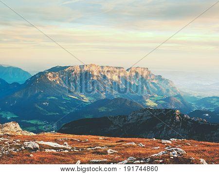Lens flare light strong effect. Morning sun between sharp rocks Alpine cliff above valley. Daybreak Sun at horizon. Mountains background