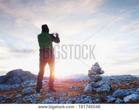 Alone Hiker Takes Phone Photo In Mountains. Man On Alps Mountain Peak.view To Purple Sky