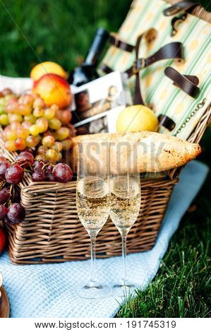 Picnic at the park on a grass delicious food: basket wine grapes peaches baguette cupcakes blue tablecloth wineglass with champagne