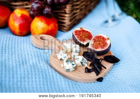 Picnic at the park. Wooden cutting board with two halves of figs basil leaves slices of Dor Blue cheese on blue tablecloth. Picnic basket and peaches on background.