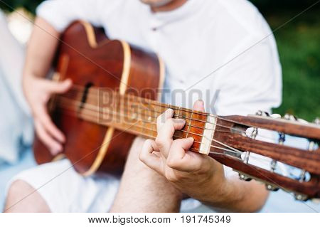 man plays guitar. wide andle. guitar neck and playing fingers foreground