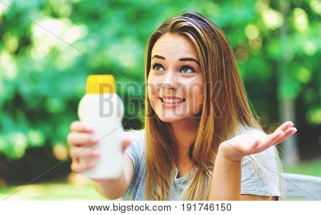 Young Woman A Bottle Of Sunblock Outside