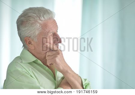Senior man standing indoors and holding hand on chin
