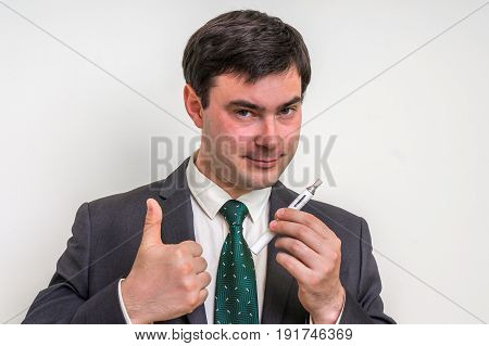 Happy businessman in suit is smoking an electronic cigarette - isolated on white