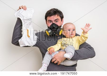 Father With Gas Mask Is Holding Stinky Diaper And Little Baby