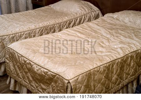 Closeup picture of two neatly done beds in hotel room