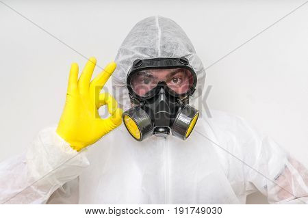 Man In Coveralls With Gas Mask Is Showing O.k. Symbol