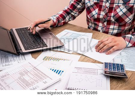 Man Filling Tax Form With Business Report, Chart, Laptop