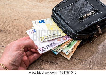 Euro Bills On Black Wallet On Wooden Desk