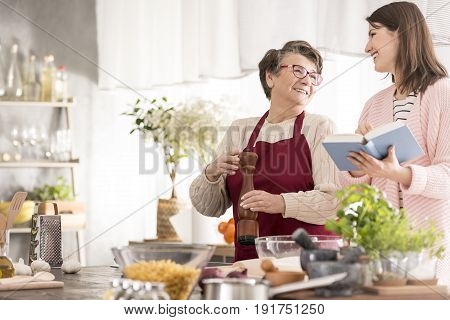 Young happy woman reading grandmother recipes cooking together