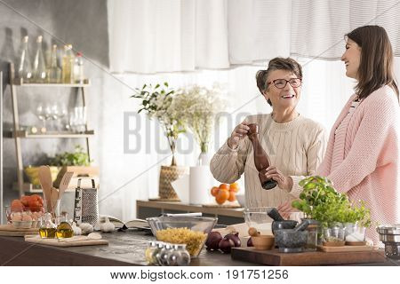 Happy grandmother and her granddaughter together in kitchen