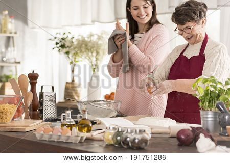 Woman cooking fresh pasta with her happy granddaughter