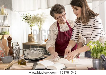Grandmother teaching her granddaughter baking cake reading recipe from book