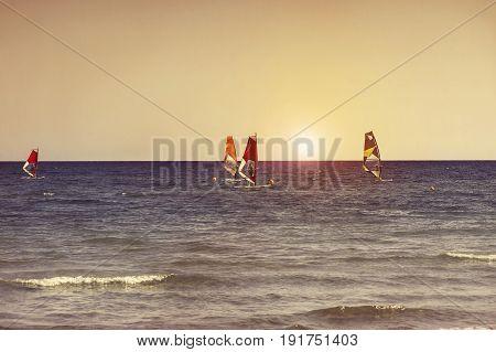 Windsurfers in the sea on Cyprus on sunset. Windsurfing in Larnaca