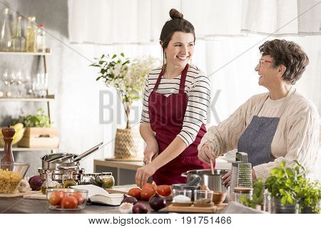 Happy young woman cooking dinner with grandmother
