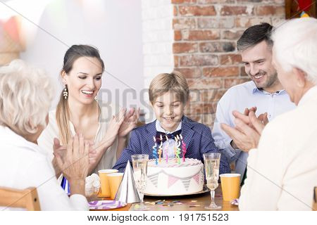 Little boy looking at birthday cake during family party