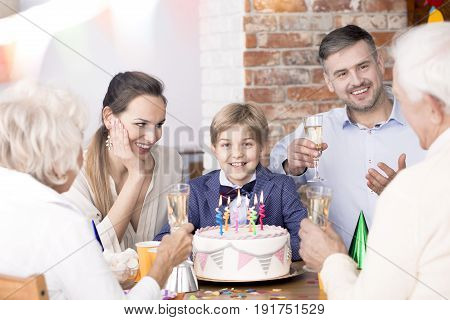 Little boy having his birthday family party with parents and grandparents