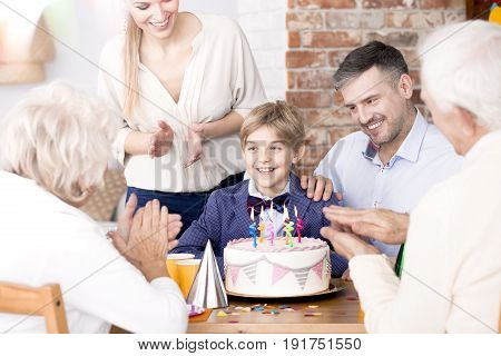Happy family clapping their hands at a little boy's birthday party