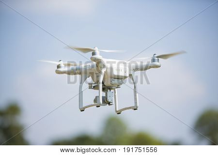Drone Quad Copter With High Resolution Digital Camera Flying Hovering In The Blue Sky