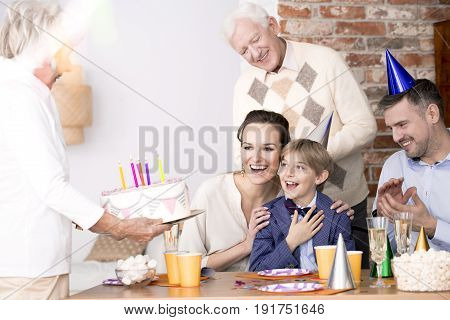Grandma bringing birthday cake to her grandson's birthday party